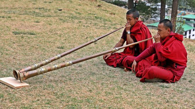 Monks practicing Dungchen trumpets on the monastery grounds