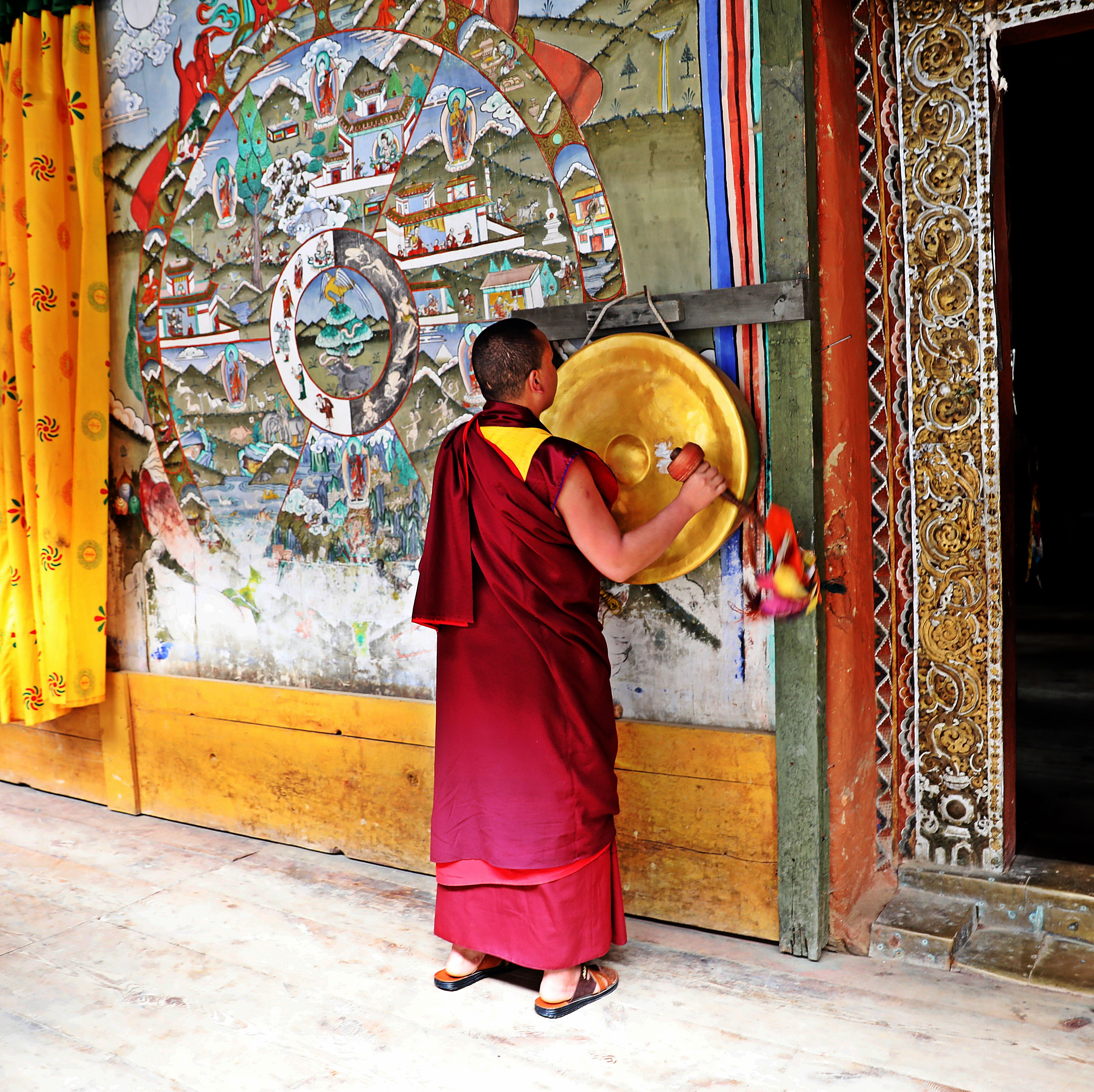 Ringing a gong to summon monks for evening chant