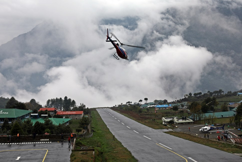 A helicopter leaving Lukla airport on a cloudy day