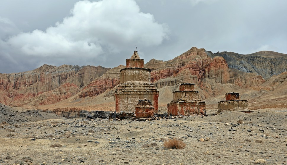 Chortens in front of red mountains