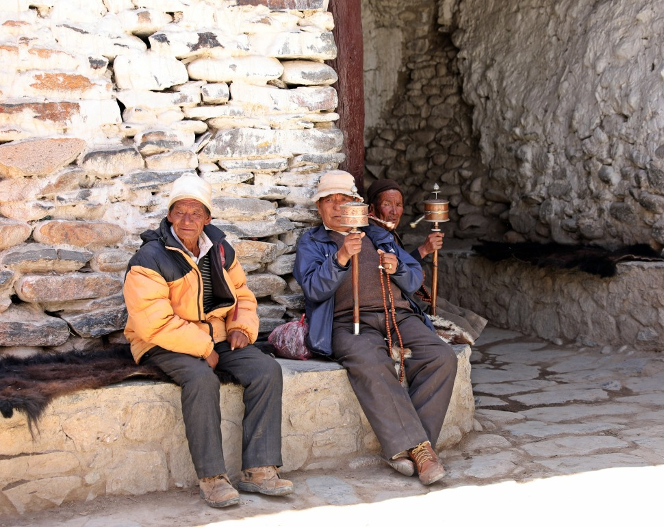 Local men spinning a hand-held prayer wheel