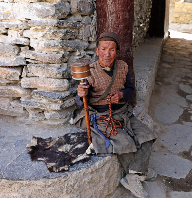 Local man spinning a hand-held prayer wheel
