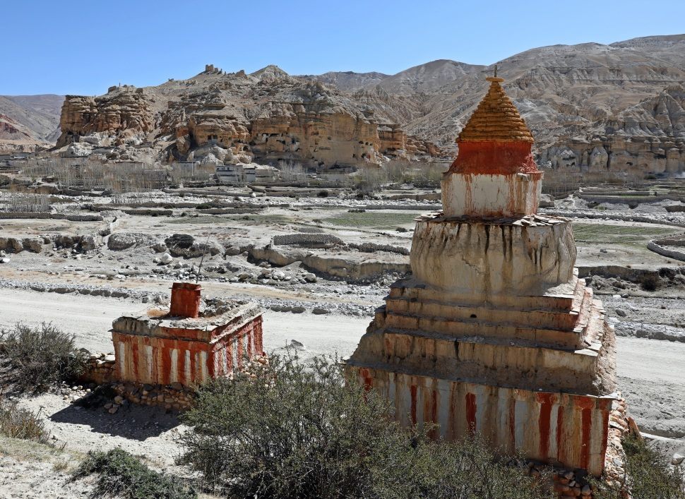 Chortens with cliff caves in the background