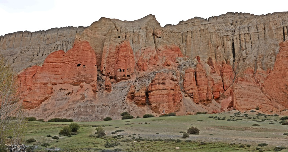 Caves in the red mountains below Ghar Gumba