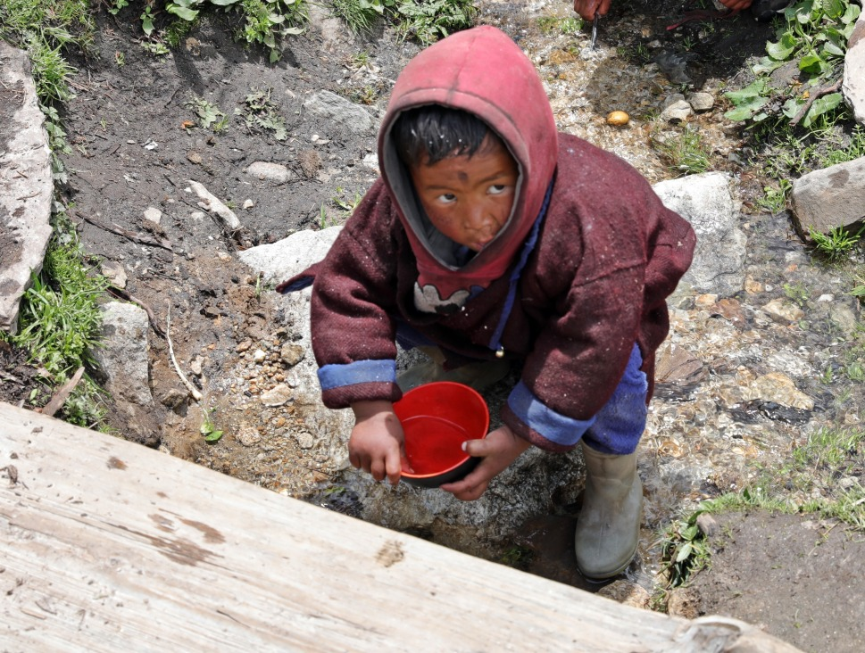 Little boy washing his bowl in a creek in Samagoan