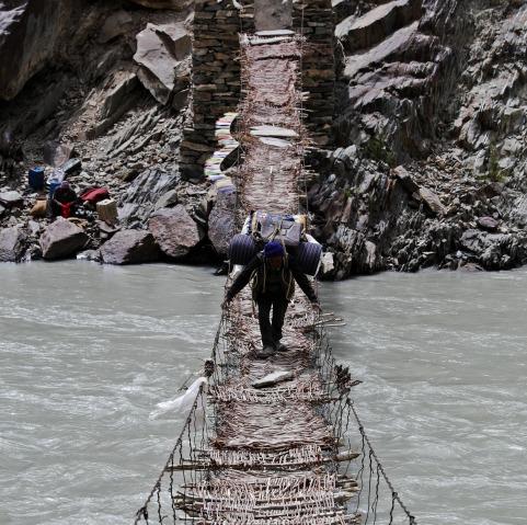 Porter crossing a twig woven bridge