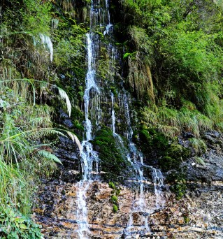 Waterfall covering the entire cliff on Kuari Pass Trek