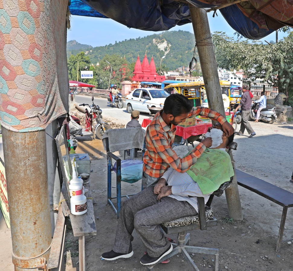 Street-side barber giving man a shave, Haridwar