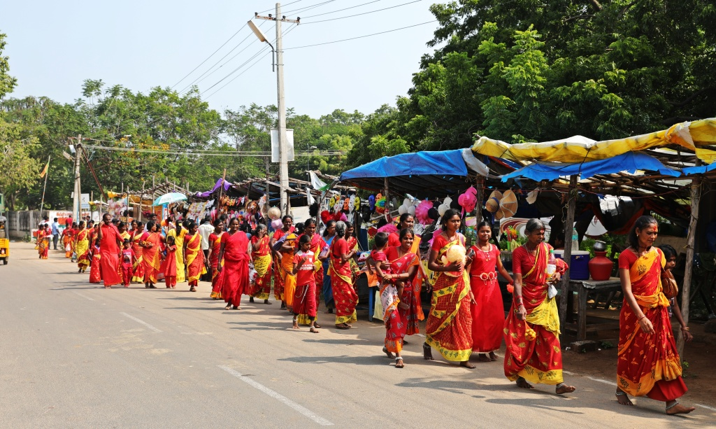 Women in red sarees walking to a temple