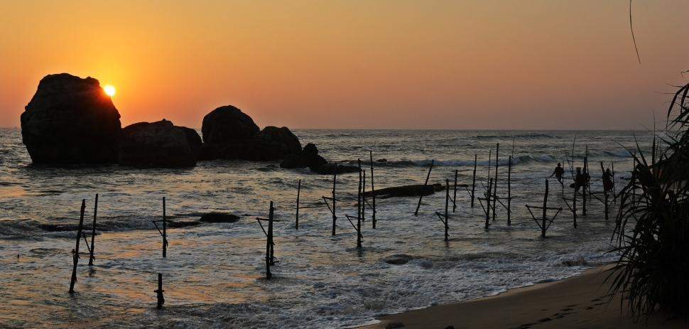 Fishermen on stilts at sunset near Ahangama
