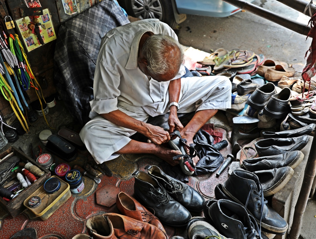 Cobbler fixing Maggie's sandal, streets of Mumbai