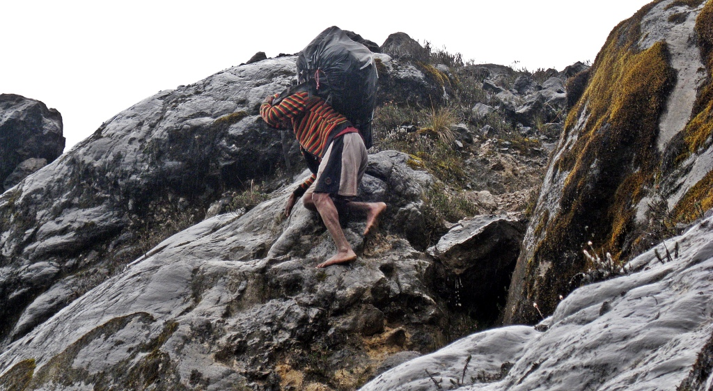A porter negotiating the sharp, cold rock, above Carstensz Pyramid basecamp