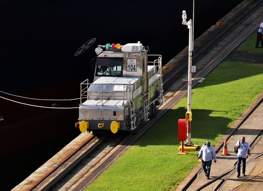 Locomotive pulling a large ship, Panama Canal