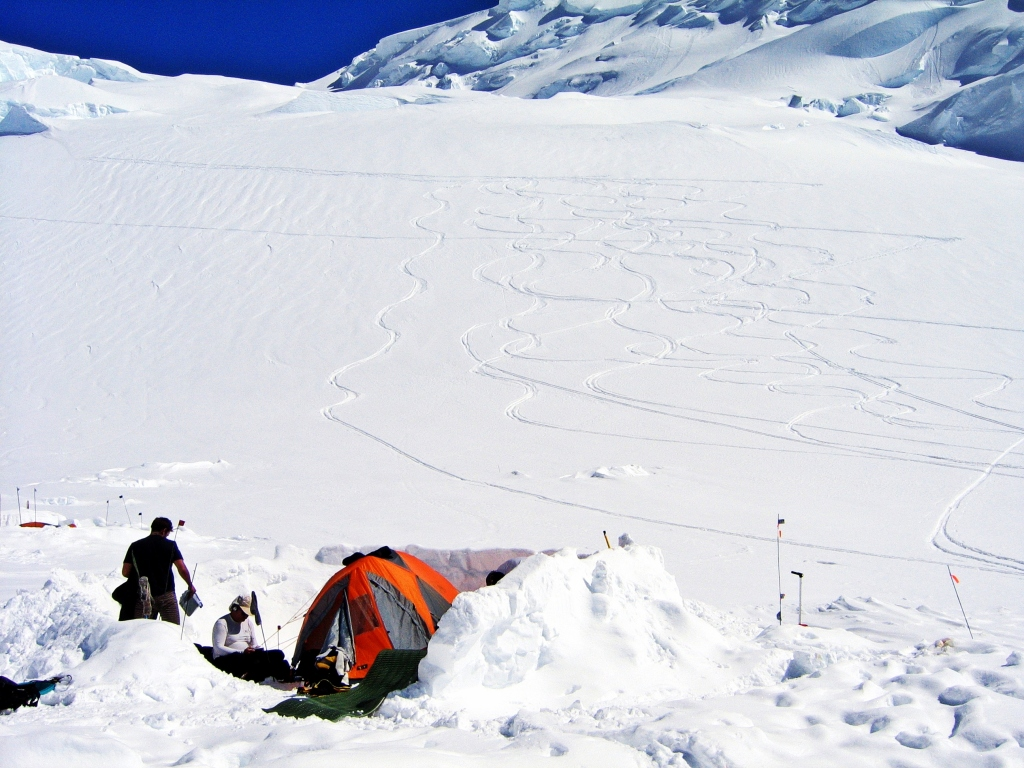 Snow wall around tent with Motorcycle Hill behind, Camp 2, Denali Climb