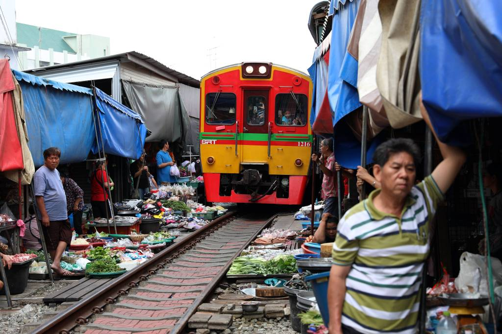Holding up an awning, Maeklong Train Market