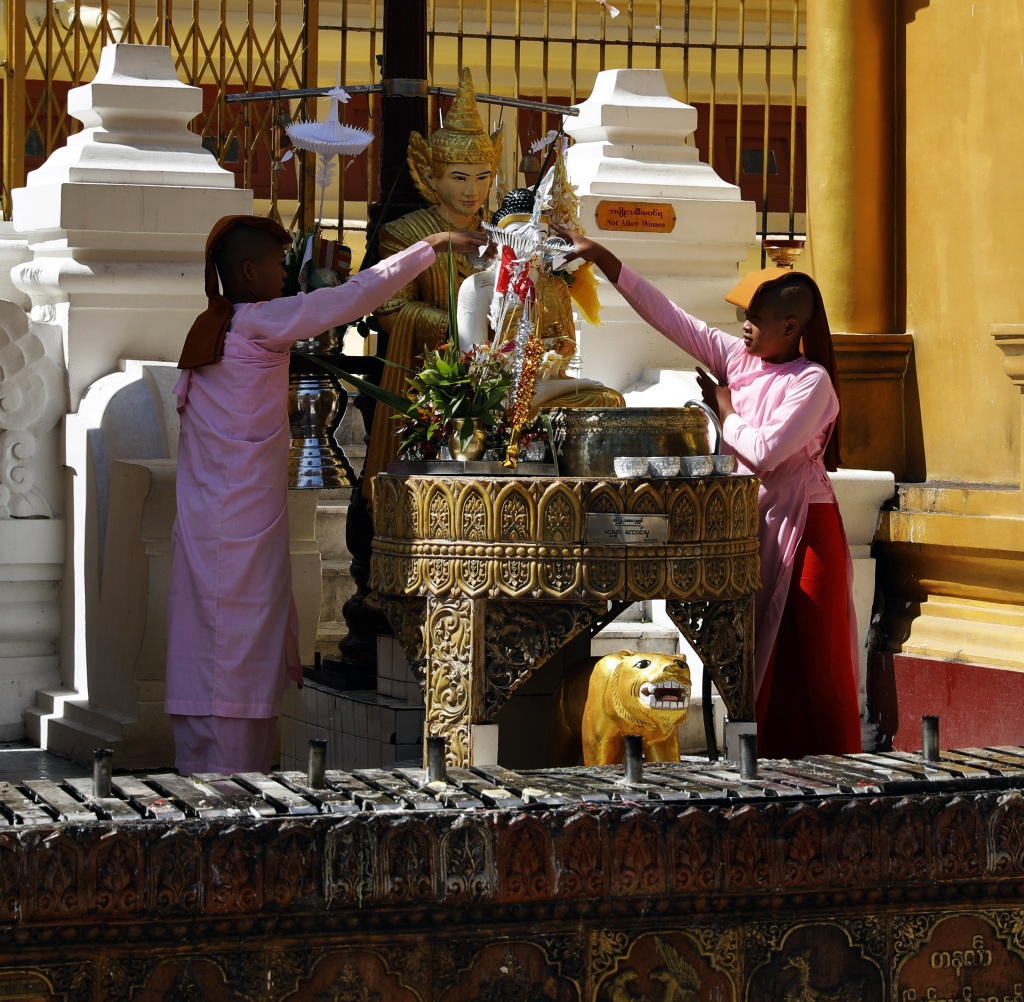 Novice nuns pouring holy water over Buddha's head